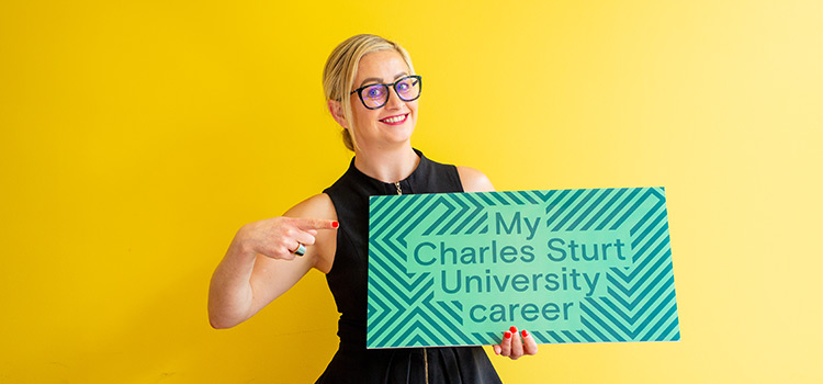 Smiling Careers Development Manager holding sign saying 'My Charles Sturt University career'