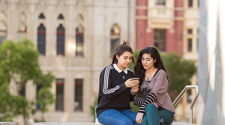 Two students looking at mobile phone